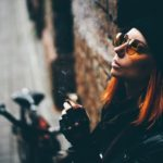 Red hair woman in black rock style leather jacket at the autumn city
